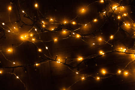 Christmas, festive background with glowing garland. Colorful lights on a dark background. New Year cards, postcard, banner. With space for text. Soft focus.
