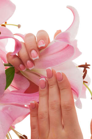 French manicure. Female young hands groomed isolated on a white background with flowers. Standard-Bild