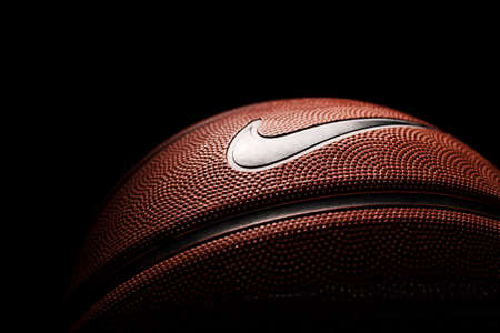 Nike brand, basketball ball Nike Baller. Orange rubber outdoor ball, ultra-durable cover, close-up on a black background.