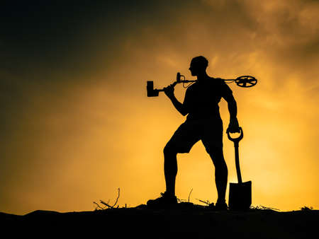 Silhouette of a man against the sunset with a metal detector and a shovel.