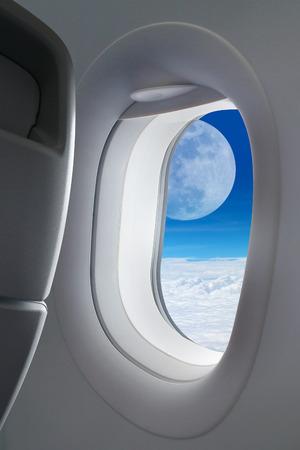 plane window: Big moon outside window plane.