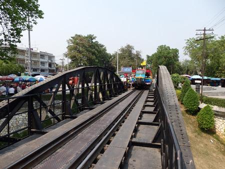 Kanchanaburi, Thailand. 17 March 2014 - Thai tourist train running cross the River Kwai bridge among the group of travellers. Editorial