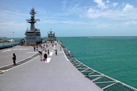 battleship: Chonburi, Thailand. 14 August 2016 - Tourist on deck of HTMS Chakri Naruebet (CVH-911) Royal Thai Naval base, Navy Aircraft Carrier at port of Sattahip, windy nation flag in sunshine and deep blue sea