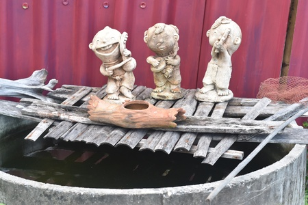 bamboo texture: Three stone dolls with bamboo texture on the water Stock Photo