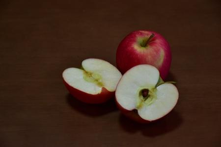fondo cafe: Dos manzanas rojas completos y cortadas con el fondo marr�n