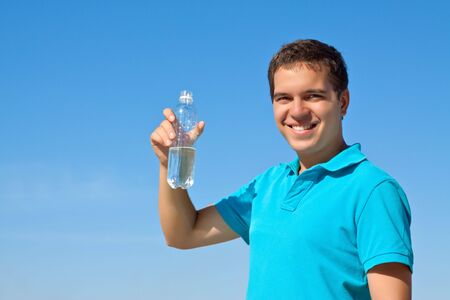 young male holding bottle of water against blue sky Stock Photo