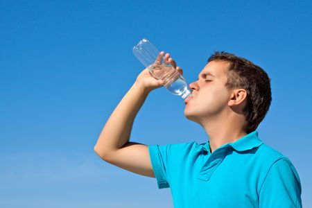 young male drinking water against blue sky Stock Photo - 7693856