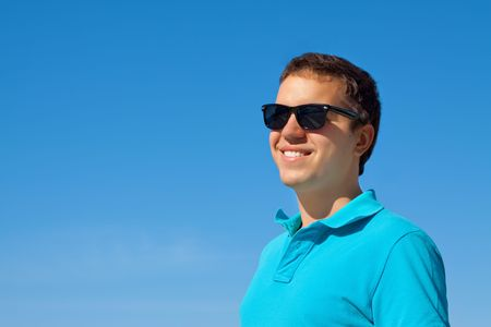 young cheerful man in sunglasses against blue sky Stock Photo - 7693860