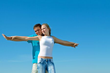 young beautiful couple embracing against blue sky Stock Photo - 7693859