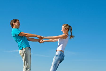young couple holding hands against blue sky Stock Photo - 7693861