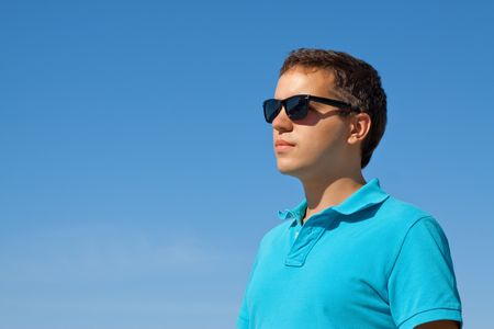 man looking at sky: young serious man in sunglasses against blue sky Stock Photo