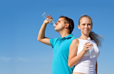 young couple with bottles of water against blue sky Stock Photo - 7693862