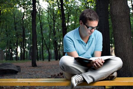 young man reading book in the park photo