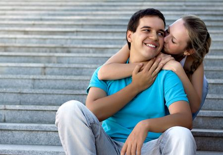 young loving couple sitting on stairs and embracing photo