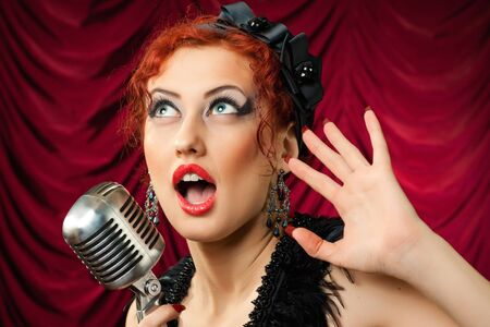 beautiful redhead woman singing into vintage microphone photo