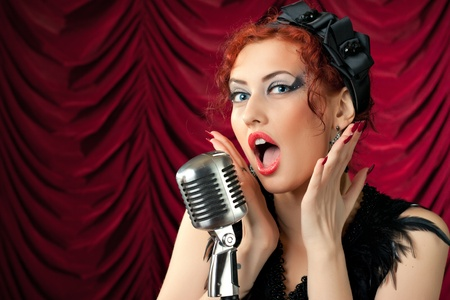 beautiful redhead woman singing into vintage microphone Stock Photo - 9254494