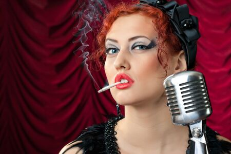 beautiful redhead woman smoking cigarette near vintage microphone photo