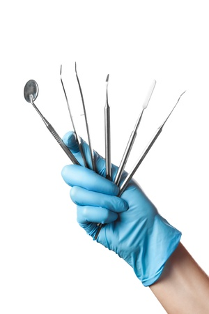 hand in blue glove holding dental tools isolated on white background photo