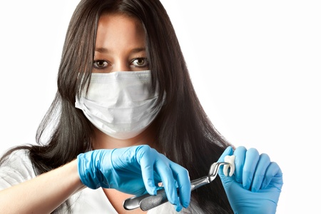 surgeon mask: female dentist in mask holding forceps and tooth isolated