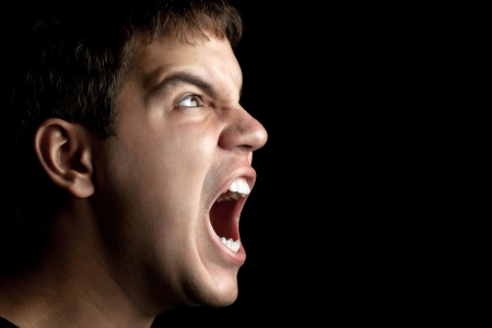 portrait of young angry man sreaming isolated on black background photo