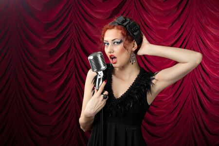 beautiful redhead woman singing into vintage microphone Stock Photo - 11138403