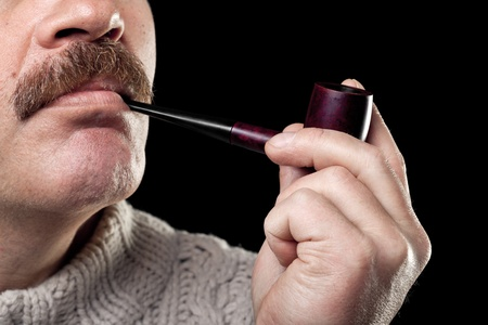 mature caucasian man holding smoking pipe in hand isolated on black background photo
