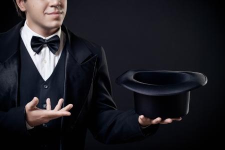 mago: Primer plano de mago mostrando trucos con sombrero de copa aislada en el fondo oscuro Foto de archivo