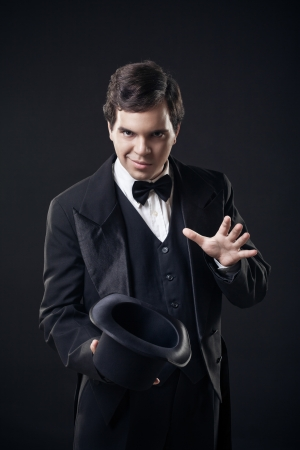 magician showing tricks with top hat isolated on dark background Banco de Imagens