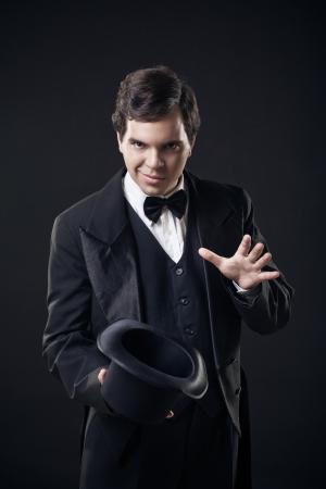 show of hands: trucchi mago che mostrano con cappello alto isolato su sfondo scuro Archivio Fotografico