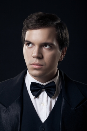 portrait of young man in tuxedo isolated on dark background photo
