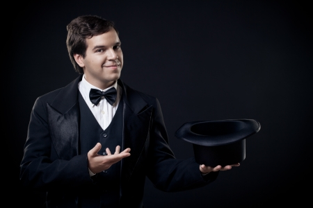 magician showing tricks with top hat isolated on dark background Stock Photo - 15070554