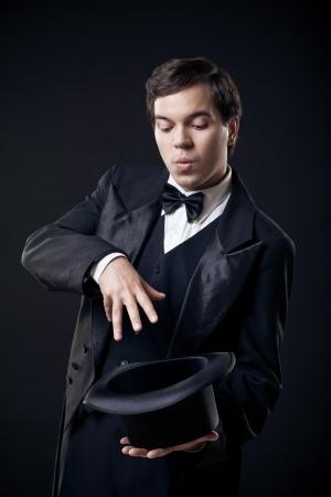mago: trucos de mago con sombrero de copa que muestra aislada en el fondo oscuro
