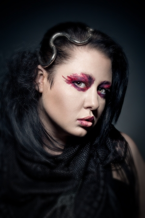 portrait of young brunette woman with fashion makeup on dark background photo