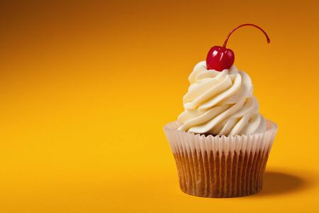 cupcake with red cherry isolated on orange background with copyspace photo