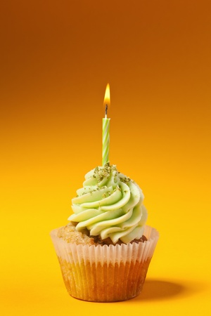 cupcake with candle isolated on orange background photo