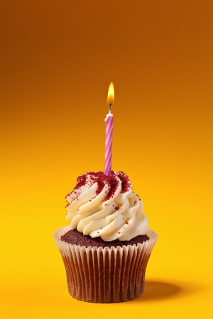 chocolate cupcake with candle isolated on orange background photo