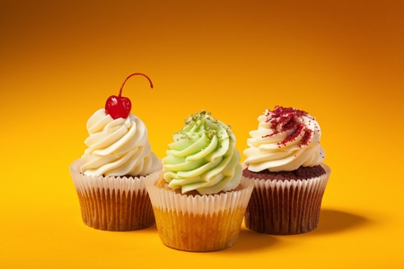 three cupcakes isolated on orange background with copyspace photo