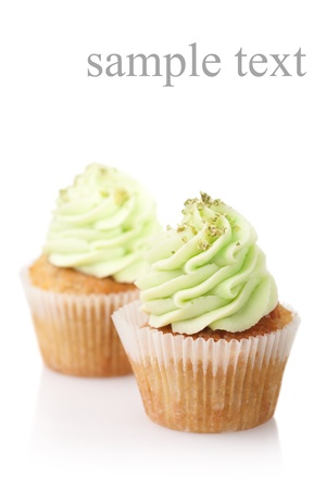 two cupcakes with green cream isolated on white background with copyspace photo