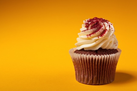 cupcakes isolated: chocolate cupcake with cream isolated on orange background with copyspace Stock Photo