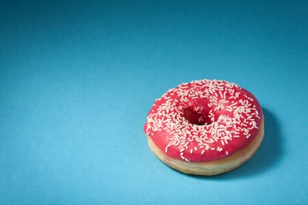 donut with red icing isolated on blue background with copyspace photo