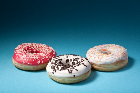 three donuts with color icing isolated on blue background with copyspace photo