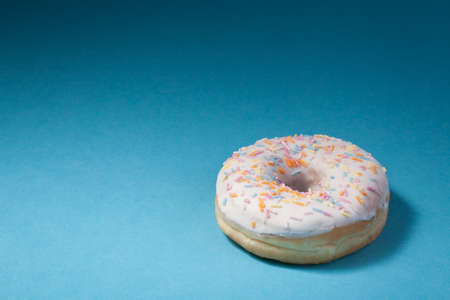 donut with white icing isolated on blue background with copyspace photo