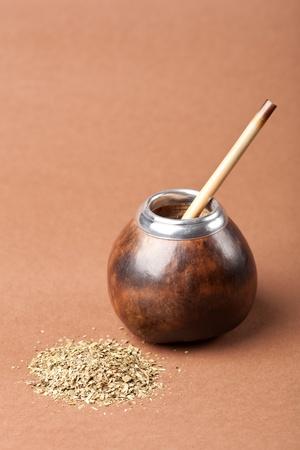 yerba mate: calabaza y bombilla con yerba mate aislados sobre fondo marr�n Foto de archivo