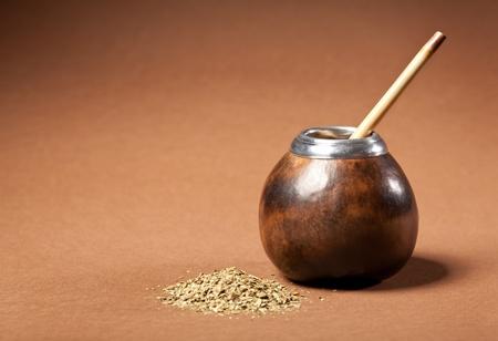 yerba mate: calabaza y bombilla con yerba mate aislados sobre fondo marrón Foto de archivo