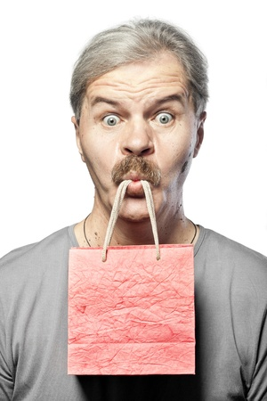 surprised mature man with shopping bag in mouth isolated on white background photo