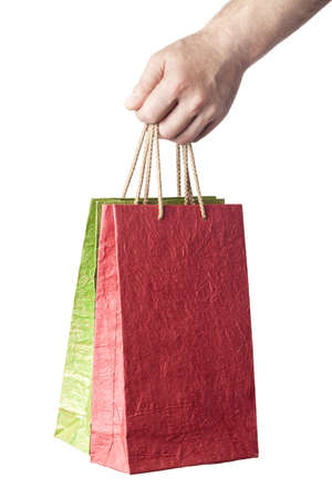 male hand holding two shopping bags isolated on white background photo