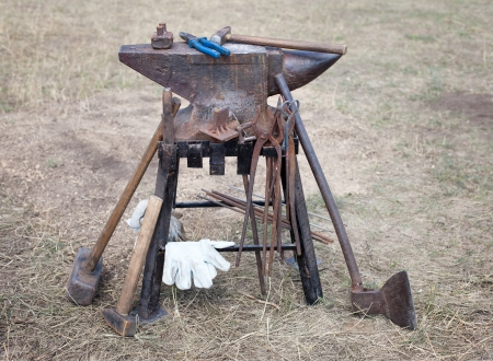 old anvil with many blacksmith tools photo