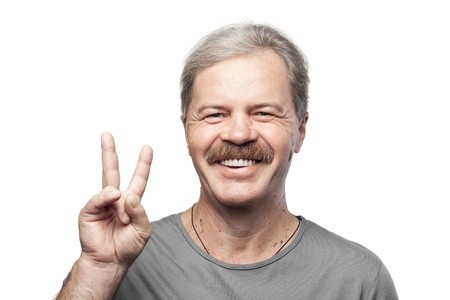 smiling mature man showing victory sign isolated on white background photo