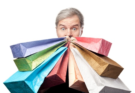 surprised mature man holding shopping bags near face isolated on white background photo
