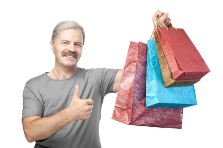 smiling mature man holding shopping bags isolated on white background photo